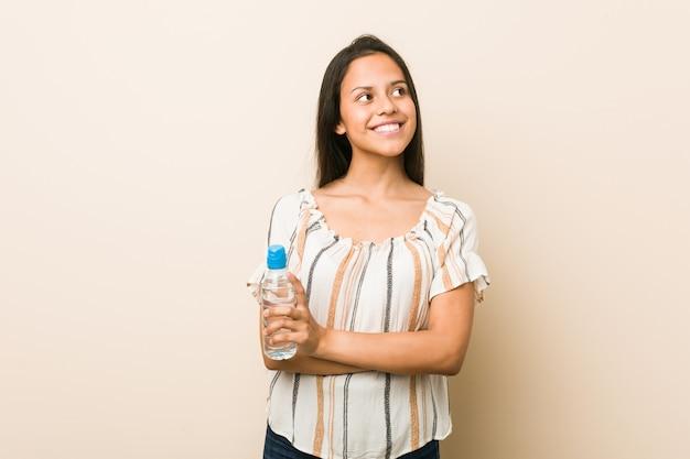 Jeune femme hispanique tenant une bouteille d'eau souriant confiant avec les bras croisés.