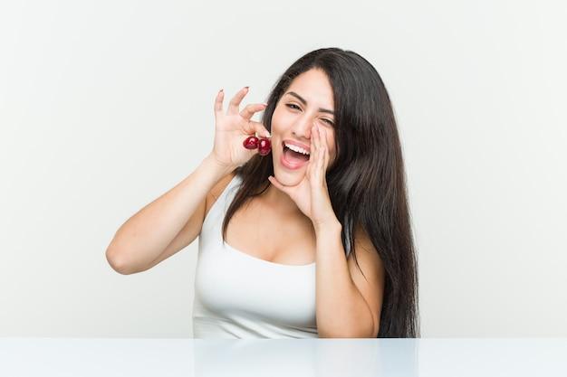 Jeune femme hispanique tenant des cerises criant excité à l'avant.