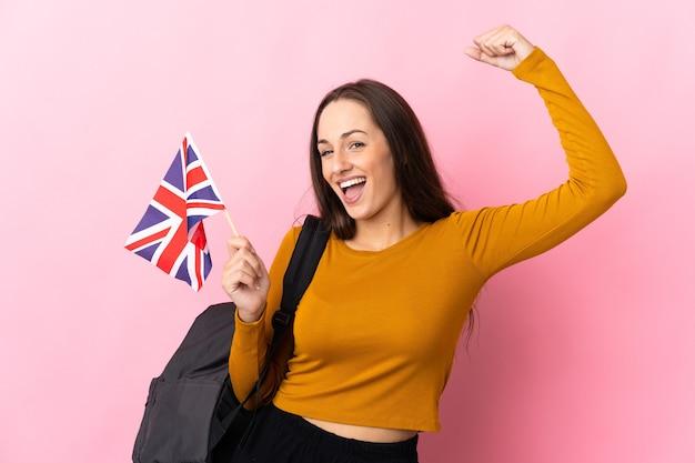 Jeune femme hispanique tenant un drapeau du royaume-uni célébrant une victoire