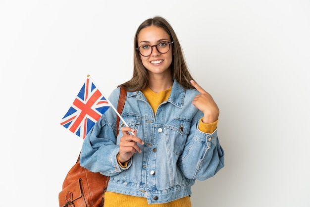 Jeune femme hispanique tenant un drapeau du royaume-uni sur fond blanc isolé donnant un geste de pouce en l'air
