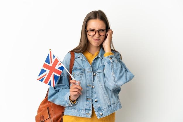 Jeune femme hispanique tenant un drapeau du royaume-uni sur fond blanc isolé frustré et couvrant les oreilles