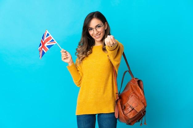 Jeune femme hispanique tenant un drapeau du royaume-uni isolé sur fond bleu faisant le geste de l'argent