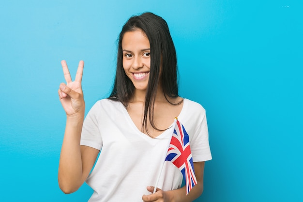 Jeune femme hispanique tenant un drapeau du royaume-uni montrant le numéro deux avec les doigts.