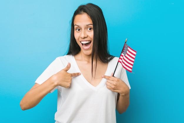Jeune femme hispanique tenant un drapeau des états-unis surpris, se montrant du doigt, souriant largement.