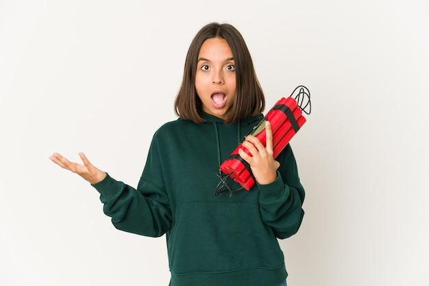 Jeune femme hispanique tenant de la dynamite recevant une agréable surprise, excitée et levant les mains.