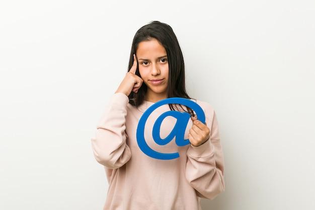 Jeune femme hispanique tenant une icône pointant son temple avec le doigt, pensant, concentré sur une tâche.