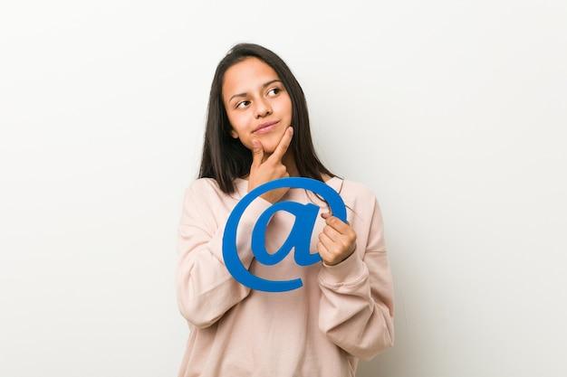 Jeune femme hispanique tenant une icône à la recherche de côté avec une expression douteuse et sceptique.