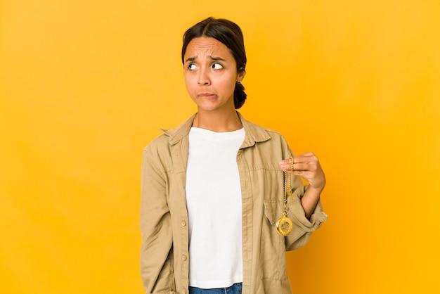 Jeune femme hispanique tenant une montre de poche confuse, se sent douteuse et incertaine.