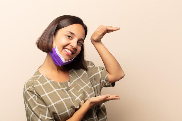 Jeune femme hispanique tenant un objet avec les deux mains sur le côté de l'espace de copie, montrant, offrant ou annonçant un objet