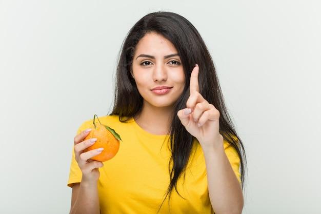 Jeune femme hispanique tenant une orange montrant le numéro un avec le doigt.