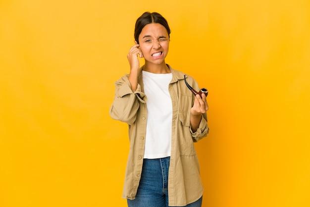 Jeune femme hispanique tenant une pipe couvrant les oreilles avec les mains.