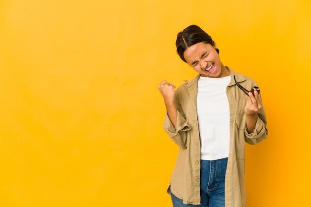Jeune femme hispanique tenant une pipe en levant le poing après une victoire, concept gagnant.