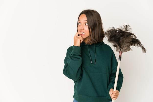Jeune femme hispanique tenant un plumeau détendu penser à quelque chose en regardant un espace de copie.