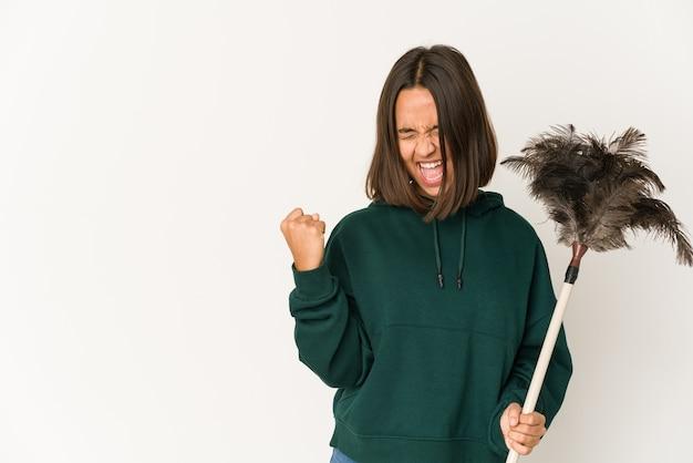 Jeune femme hispanique tenant un plumeau en levant le poing après une victoire, concept gagnant.