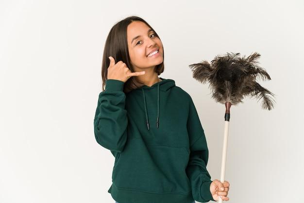 Jeune femme hispanique tenant un plumeau montrant un geste d'appel de téléphone mobile avec les doigts