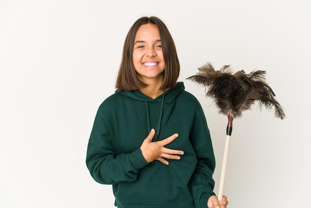 Jeune femme hispanique tenant un plumeau en riant et en s'amusant.