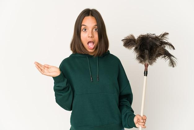 Jeune femme hispanique tenant un plumeau surpris et choqué.