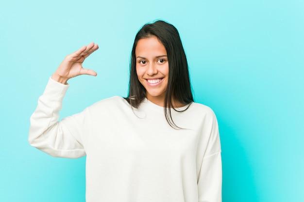 Jeune femme hispanique tenant quelque chose de peu avec les index, souriant et confiant.