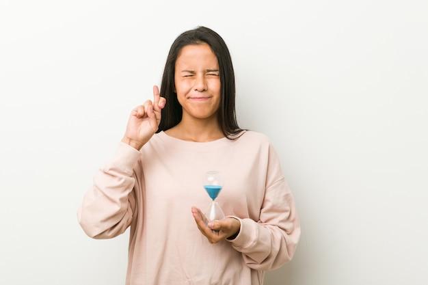 Jeune femme hispanique tenant un sablier croise les doigts pour avoir de la chance