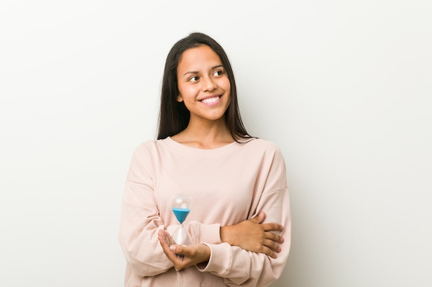 Jeune femme hispanique tenant un sablier souriant confiant avec les bras croisés.