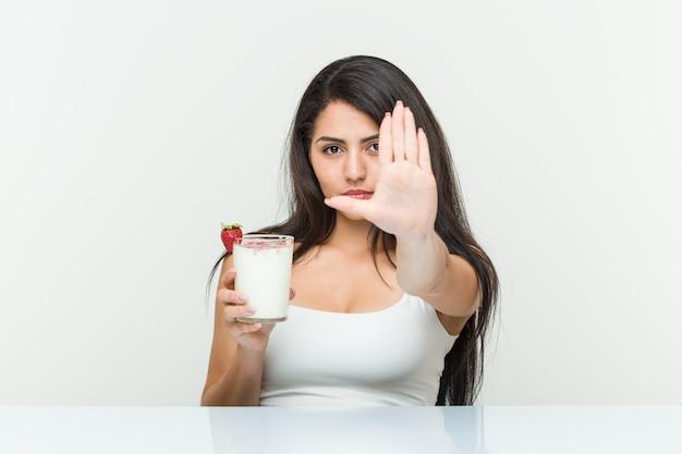 Jeune femme hispanique tenant un smoothie jeune femme hispanique tenant un toast à l'avocat debout avec la main tendue montrant un panneau d'arrêt vous empêchant.