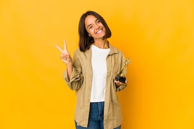 Jeune femme hispanique tenant une statuette de prix joyeux et insouciant montrant un symbole de paix avec les doigts