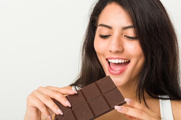 Jeune femme hispanique tenant une tablette de chocolat