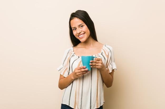 Jeune femme hispanique tenant une tasse heureuse, souriante et gaie.