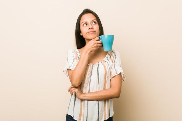 Jeune femme hispanique tenant une tasse à la recherche sur le côté avec une expression douteuse et sceptique
