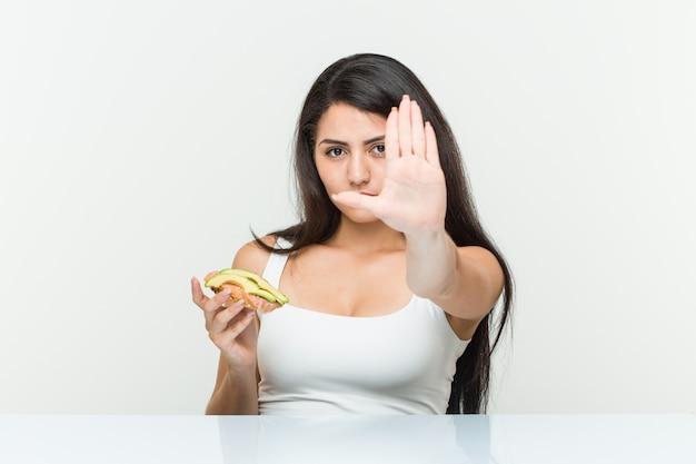 Jeune femme hispanique tenant un toast à l'avocat debout avec la main tendue montrant le panneau d'arrêt, vous empêchant.