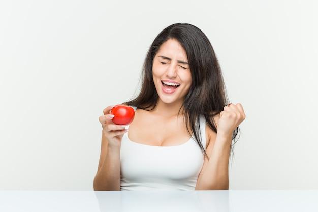 Jeune femme hispanique tenant une tomate acclamant insouciant et excité. la victoire .