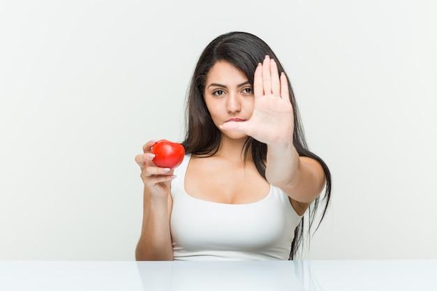 Jeune femme hispanique tenant une tomate debout avec la main tendue montrant le panneau d'arrêt, vous empêchant.