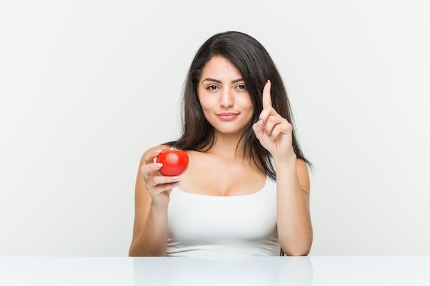 Jeune femme hispanique tenant une tomate montrant le numéro un avec le doigt.