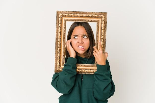 Jeune femme hispanique tenant un vieux cadre couvrant les oreilles avec les mains.