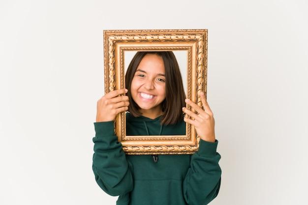 Jeune femme hispanique tenant un vieux cadre heureux, souriant et joyeux.