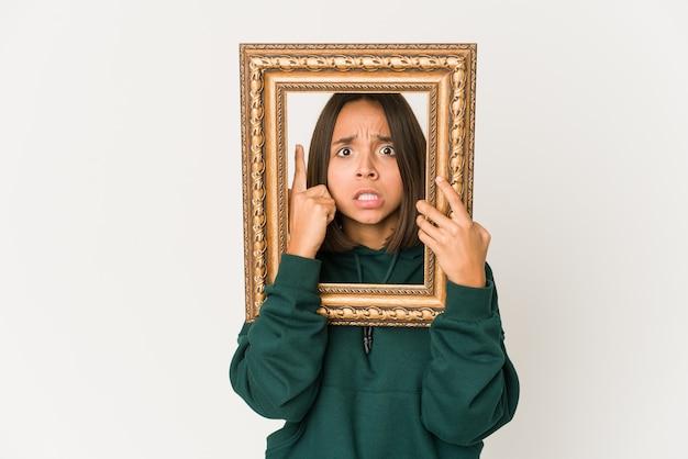 Jeune femme hispanique tenant un vieux cadre montrant un geste de déception avec l'index.