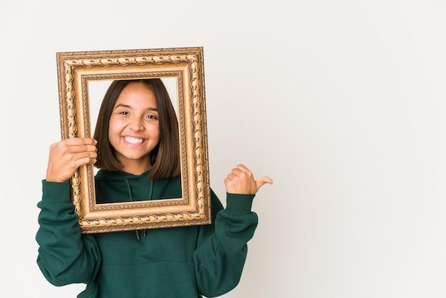 Jeune femme hispanique tenant un vieux cadre pointe avec le pouce, riant et insouciant.