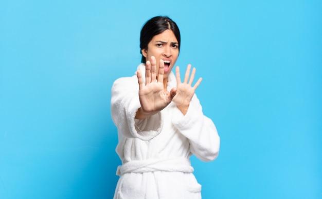 Jeune femme hispanique terrifiée, reculant et hurlant d'horreur et de panique, réagissant à un cauchemar