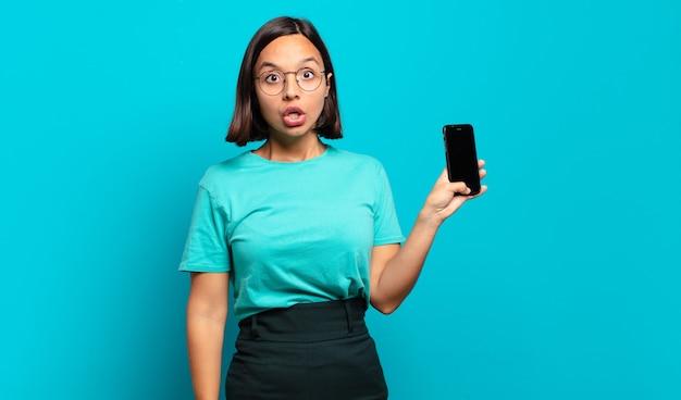 Jeune femme hispanique à très choqué ou surpris, regardant la bouche ouverte en disant wow