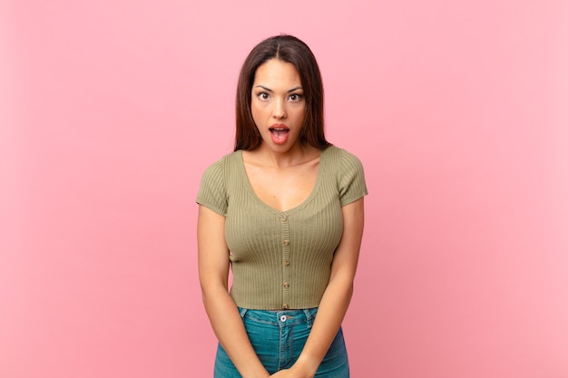 Jeune femme hispanique à très choqué ou surpris