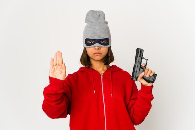 Jeune femme hispanique de voleur portant un masque debout avec la main tendue montrant un panneau d'arrêt, vous empêchant.