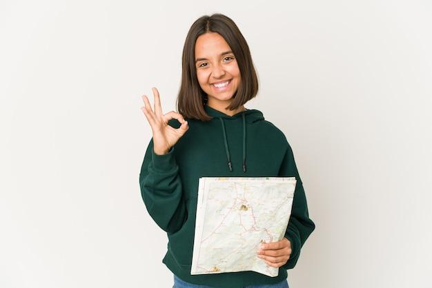 Jeune femme hispanique voyageur tenant une carte joyeuse et confiante montrant le geste ok