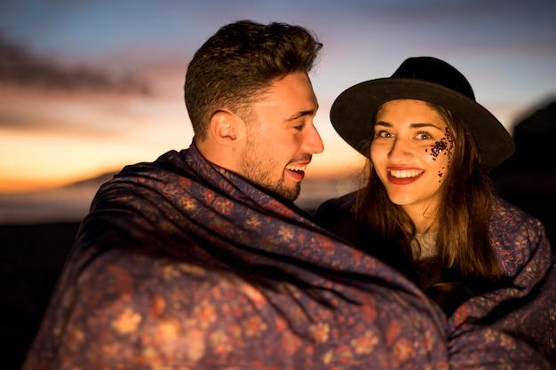Jeune femme avec un homme en couverture au bord de la mer