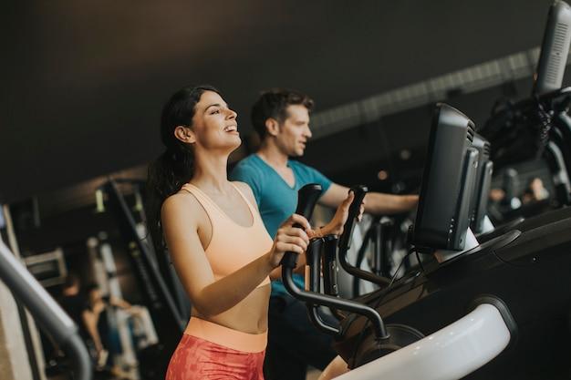 Jeune, femme, homme, sur, elliptique, stepper, entraîneur, exercisme, dans, gymnase