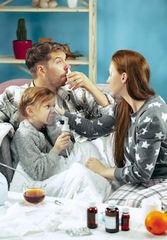 La jeune femme et l'homme avec une fille malade à la maison. traitement à domicile. se battre avec une maladie. santé médicale. la vie de la famille. l'hiver, la grippe, la santé, la douleur, la parentalité, le concept de relation