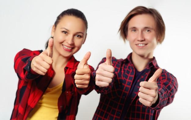 Jeune femme et homme heureux montrent les pouces vers le haut de geste. sur blanc. mains au point, visage flou