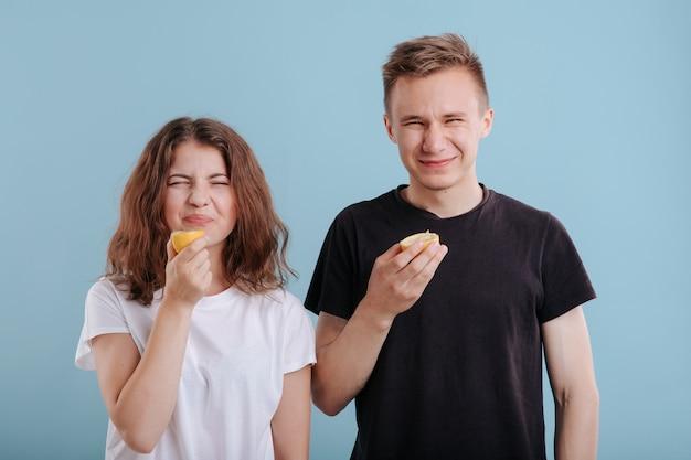 Jeune femme et homme mangeant une tranche de citron