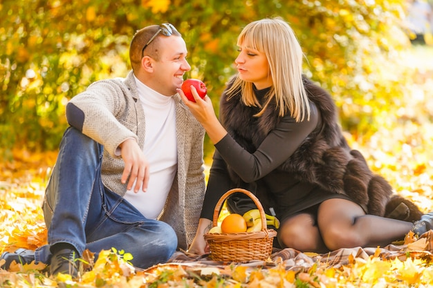 Jeune femme et homme marchant dans le parc de la ville en automne