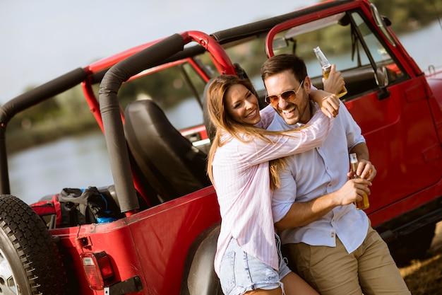 Jeune femme et homme s'amuser en plein air près d'une voiture rouge à la journée d'été