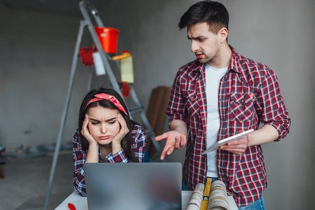 Jeune femme et homme se disputant pendant la rénovation de l'appartement